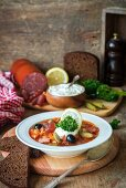 Solyanka (Traditional Russian meat soup from different kinds of meat and sausages with pickled cucumber and lemon)