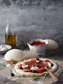 An unbaked pizza with tomato, black olives and mozzarella