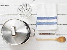 Kitchen utensils: cooking pot, measuring cup, wooden spoon, fork, kitchen towel