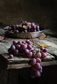 Fresh bunch of red grapes on wooden table
