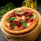 Pizza with tomato sauce, Capicola and mozzarella with basil leaves