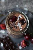 Chocolate coconut smoothie in a jar topped with cherry, dark chocolate, coconut flakes and cacao nibs