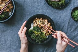 Chicken stir fry with roasted broccoli, hands with chopsticks