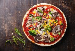 Vegetarian pizza with mushrooms and ruccola on wooden table