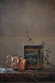 Copper cups and vintage tin on wooden table