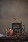 Holztisch mit Kupfertassen und Vintage-Dose