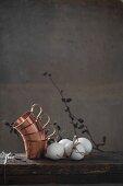 Holztisch mit gestapelten Kupfertassen und weissen Hühnereiern