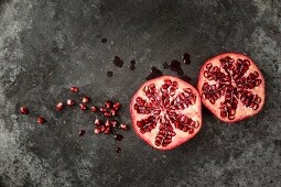Two halves of a pomegranate and seeds and juice on a grey metal surface