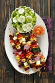 Sausage and vegetable skewers with cucumber salad (seen from above)