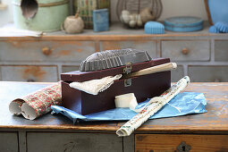 Old cake tin on wooden box and vintage wrapping paper