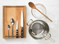 Various kitchen utensils: pot, strainer, measuring cup, spoons, knives