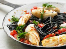 Black pasta with squid and tomatoes