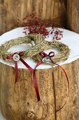 Two hay rings decorated with red bows on a white tree trunk surface