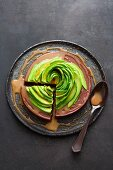 A chocolate and passion fruit cake topped with an avocado rose and caramel and rum syrup