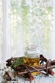 Glass jar of hot herbal tea with bunch of fresh thyme, served with vintage tea-strainer on old wooden stool