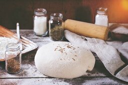 Dough on wooden table with flour, rolling-pin and jars with backing ingredients