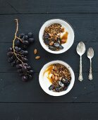 Bowls of oat granola with yogurt, fresh grapes, almond and honey over black wooden backdrop