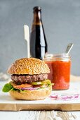 Fresh homemade burger on white wooden serving board with onion rings, salsa sauce and bottle of beer
