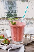 Glass of red strawberry smoothie with chia seeds, served with retro cocktail tube, fresh mint and strawberries