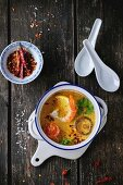 White Ceramic pan with Spicy Thai soup Tom Yam with Coconut milk, Chili pepper and Seafood