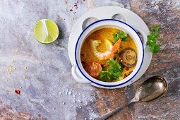 White Ceramic pan with Spicy Thai soup Tom Yam with Coconut milk, Chili pepper and Seafood over gray stone background