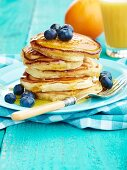 Pancake stack with maple syrup and blueberries and orange juice