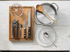 Various kitchen utensils: pot, measuring cup, can opener, knives, spoons