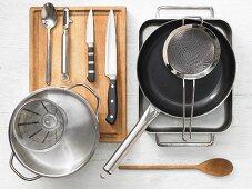 Various kitchen utensils: baking dish, pan, sieve, pot, measuring cup, knives