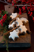 Cinnamon stars and cinnamon sticks on a wooden board