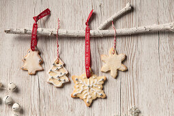 Edible iced Christmas tree and snowflake shaped biscuits hanging by Noel red ribbon and bakers twine from a white branch