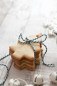 A Stack of tree shaped biscuits tied with blue and white bakers twine in a white Christmas setting