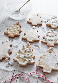 Tree shaped Christmas biscuits being decorated with white icing and christmas sprinkles bakers twine in the forground and icing bowl and silver sppon in the background