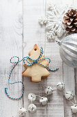 Stack of Christmas Tree shaped biscuits tied with blue and white bakers twine on a white wood rustic christmas setting