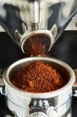 Freshly ground coffee falls from a coffee mill into a filter holder