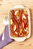 Sausages baked with onion, apple and apricot jam
