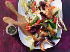 A salad with chicory, green asparagus, prawns and chia seeds
