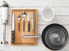 Various kitchen utensils: hand blender, knives, spoons, pan, glass bowls