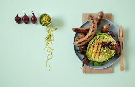 Grilled savoy cabbage with citrus and garlic butter, toasted onions and grilled sausages
