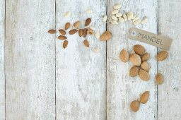 Almonds with a brown paper label on a wooden background (top view)