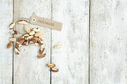 Brazil nuts with a brown paper label on a wooden background (top view)