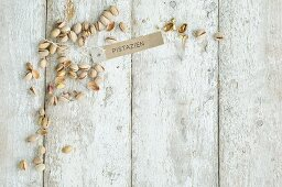 Pistachios with a brown paper label on a wooden background (top view)