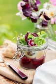 Salad with beetroot puree and marinated feta in glass jar for a picnic