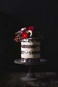 Layered wedding cake on stand decorated witih fresh flowers and gold donuts