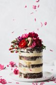 Wedding cake with buttercream, flowers, and gold donuts