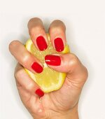 A woman's hand with red fingernails squeezing half a lemon