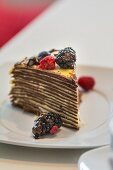 A slice of pancake cake with berries and chocolate sauce