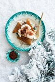 Festive gingerbread cake with whipped cream on a plate in the snow