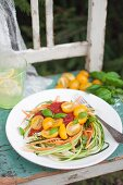Vegan raw zucchini and carrot noodles (vegetable pasta) with tomato sauce, cherry tomatoes and fresh basil leaves
