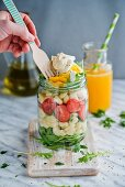 Pasta salad with tomatoes, egg and rocket in a glass jar
