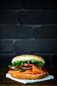 A bagel with smoked salmon, cucumber, tomato and rocket